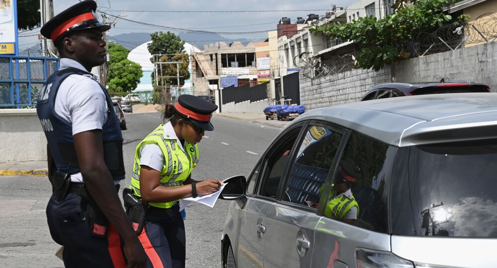 Two Jamaica Constabulary Force officers conduct a traffic stop in the Half Way Tree neighborhood of the capital, Kingston