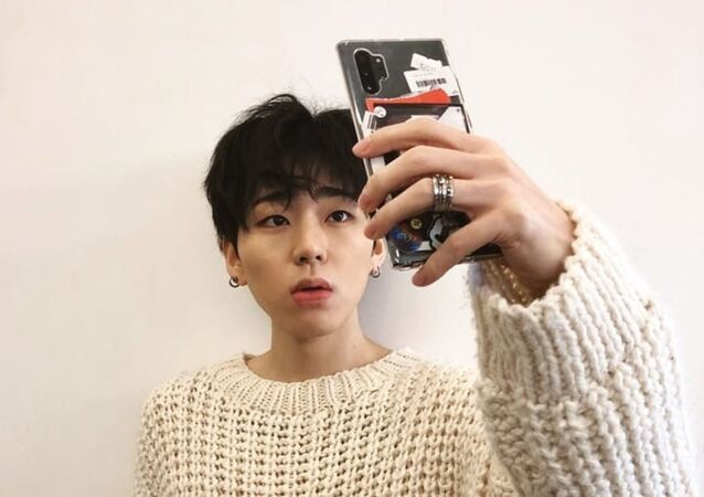 Zico poses as he takes a selfie.