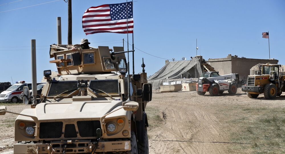A U.S. soldier, left, sits on an armored vehicle behind a sand barrier at a newly installed position near the tense front line between the U.S-backed Syrian Manbij Military Council and the Turkish-backed fighters, in Manbij, north Syria, Wednesday, April 4, 2018.