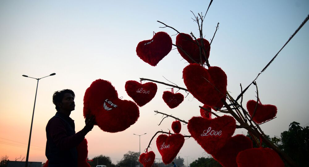 An Indian vendor adjusts heart-shaped pillows hanging from a tree at a roadside stall ahead of Valentine's Day in Jalandhar on February 9, 2018.