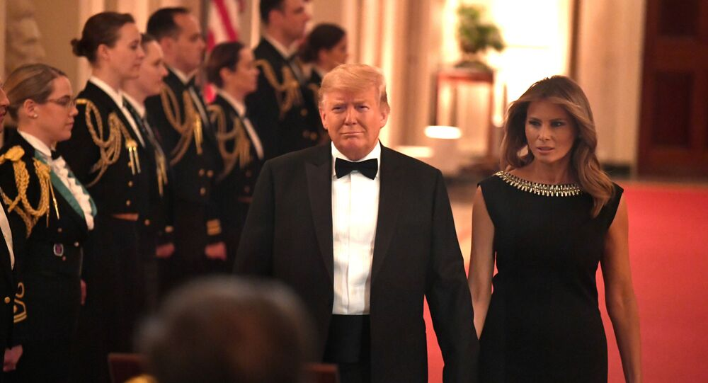 U. S. President Donald Trump holds hands with first lady Melania Trump as they arrive to host the Governors Ball in the East Room of the White House, Washington, DC, U.S., February 9, 2020