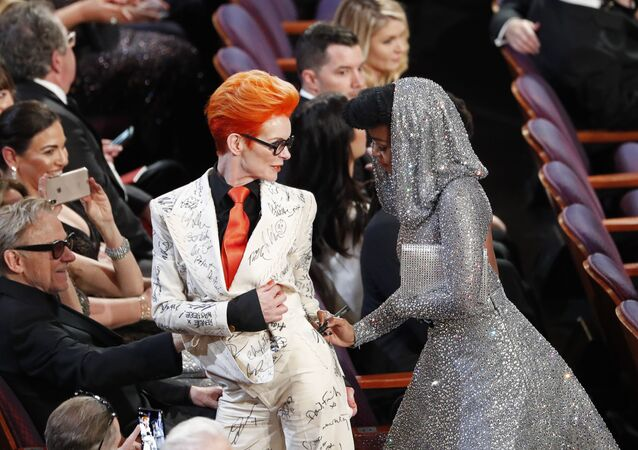 Janelle Monae signs Sandy Powell's outfit during the Oscars show at the 92nd Academy Awards in Hollywood, Los Angeles, California, U.S., February 9, 2020.