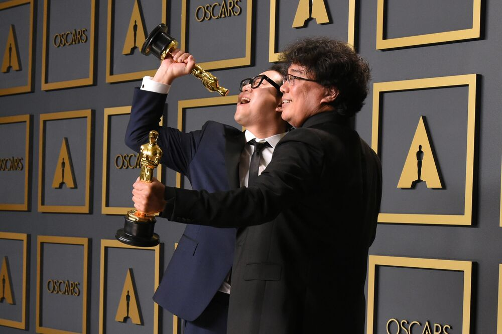 Parasite writers Han Jin-won (L) and Bong Joon-ho pose in the press room with the Oscars for Parasite during the 92nd Oscars at the Dolby Theatre in Hollywood, California on 9 February 2020. Bong Joon-ho won for Best Director, Best Movie, Best Foreign Film and Best Original Screenplay for Parasite.