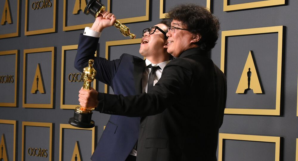 Parasite writers Han Jin-won (L) and Bong Joon-ho pose in the press room with the Oscars for Parasite during the 92nd Oscars at the Dolby Theater in Hollywood, California on February 9, 2020. - Bong Joon-ho won for Best Director, Best Movie, Best International Feature Film and Best Original Screenplay for Parasite.