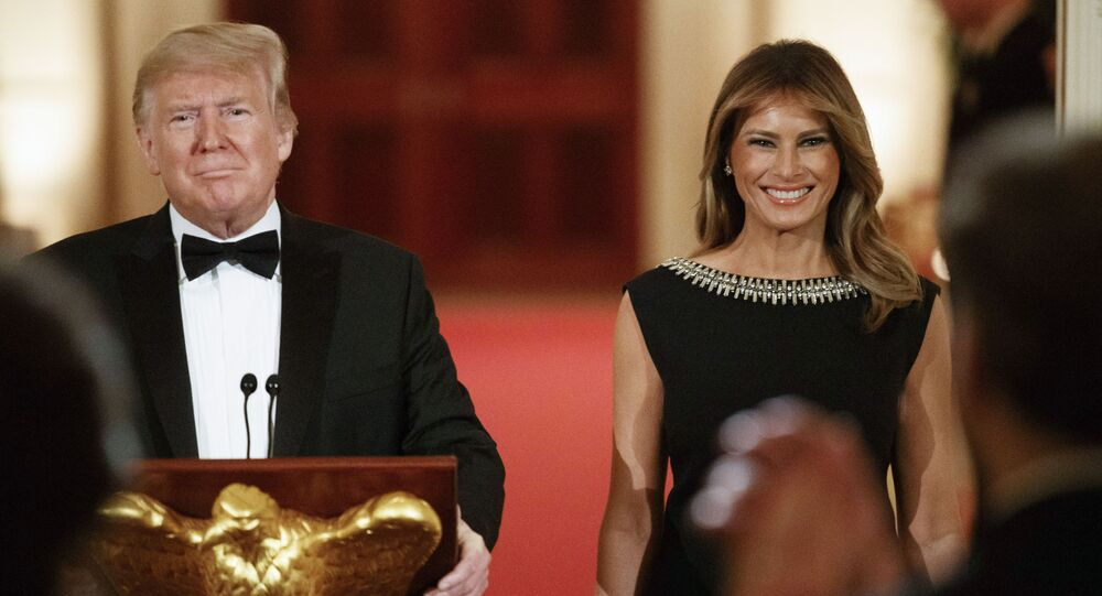 First lady Melania Trump smiles next to President Donald Trump as he arrives to speak at the Governors' Ball