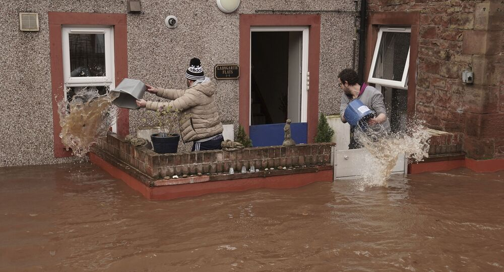 Men try to control the flow of flood water, outside a property, in Appleby-in-Westmorland, as Storm Ciara hits the UK, in Cumbria, England, Sunday Feb. 9, 2020