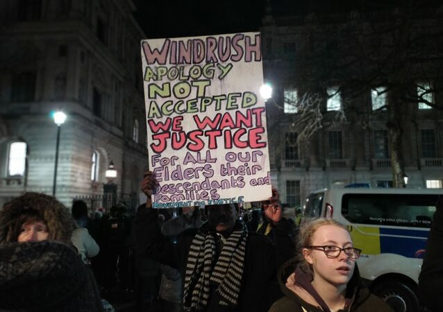 Man holds placard outside Number 10 in crowd demanding justice for Windrush generation 10 Feb 2020