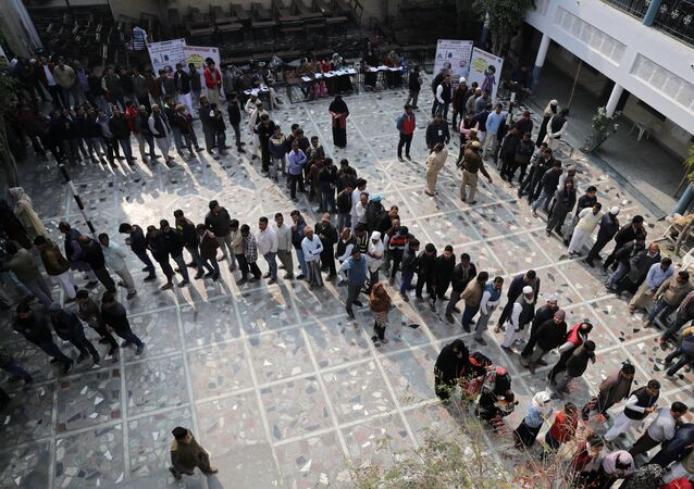 Voters stand in queues as they wait to cast their vote outside a polling booth during the state assembly election, in Shaheen Bagh, New Delhi, India, February 8, 2020.