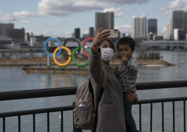 A woman takes a selfie with her son in front of the Olympic rings in Tokyo's Odaiba district.