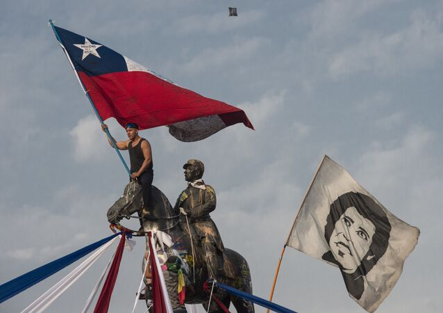 A demonstrator waves a Chilean national flag next to another flag depicting late Chilean musician Victor Jara during a protest against President Sebastian Pinera's government, in Santiago, on January 17, 2020
