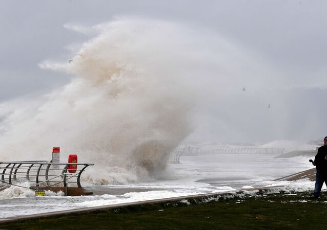 A man looks out to the sea as a wave crashes over the barrier onto the promenade in Blackpool, northern England, on February 10, 2020 as high winds brought by Storm Ciara continue