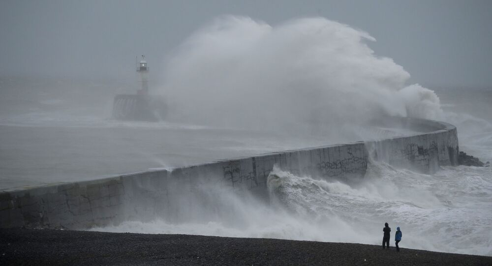 Waves crash over the harbour wall by a lighthouse as Storm Ciara hits Newhaven, on the south coast of England, Sunday, Feb. 9, 2020