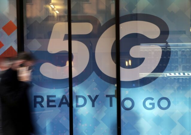 A man walks past a 5G sign in Monaco, November 28, 2019