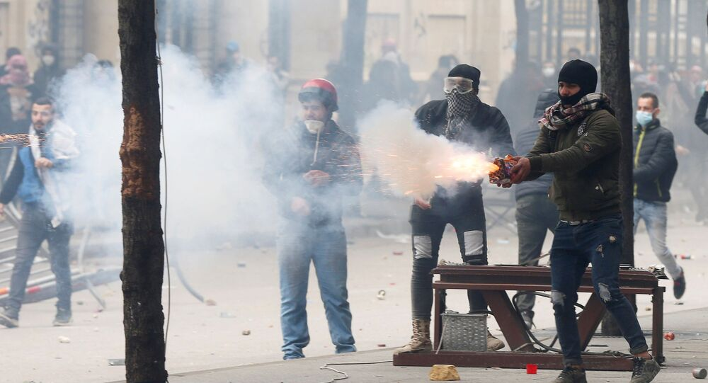 A protestor throws fireworks to the riot police during a protest seeking to prevent MPs and government officials from reaching the parliament for a vote of confidence, in Beirut, Lebanon February 11, 2020