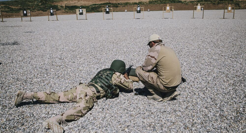 In this March 9, 2016 file image, a Dutch army trainer, right, helps a Kurdish Peshmerga soldier during a military training session at a shooting range, at Bnaslawa Military Base in Irbil, northern Iraq.