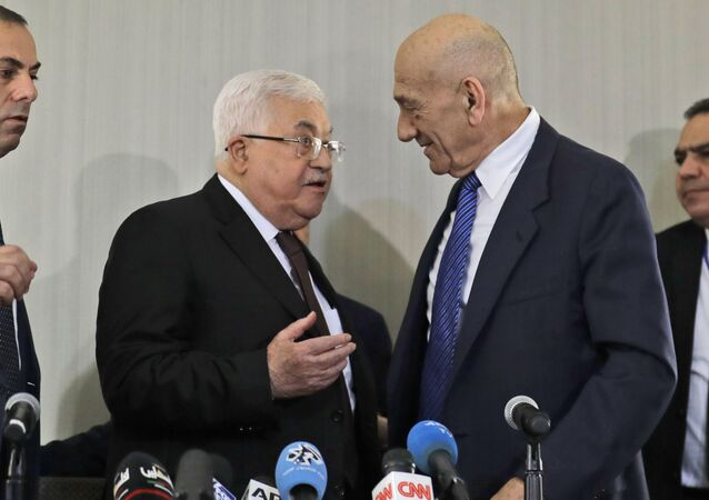 Palestinian President Mahmoud Abbas, left, speaks with former Israeli Prime Minister Ehud Olmert after a news conference in New York