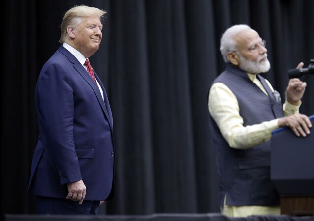 President Donald Trump listens as India Prime Minister Narendra Modi introduces him
