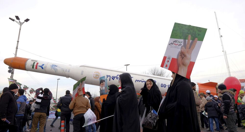 People gather around a model of a satellite-carrier rocket displayed during a ceremony  marking the 37th anniversary of the Islamic Revolution, in Tehran February 11, 2016