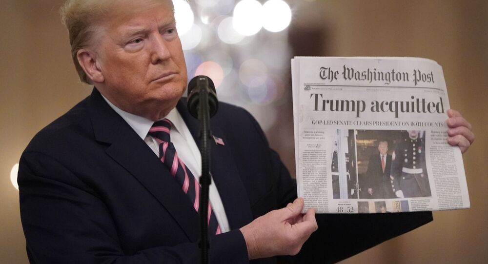U.S. President Donald Trump holds up a copy of the Washington Post's front page showing news of Trump's acquitttal in his Senate impeachment trial, as he delivers a statement about his acquittal in the East Room of the White House in Washington, U.S., February 6, 2020.