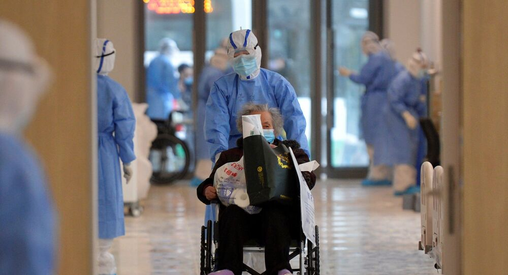 A medical worker in protective suit moves a novel coronavirus patient in a wheelchair at a hospital in Wuhan