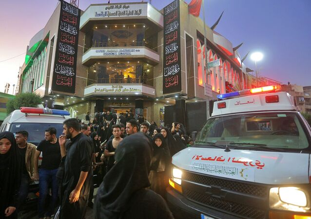 People gather outside a hospital while ambulances bring injured people after a walkway collapsed and set off a stampede as thousands of Shiite Muslims marked one of the most solemn holy days of the year in the holy city of Karbala, Iraq, Tuesday, Sept. 10, 2019