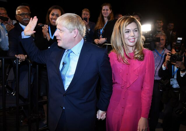 Britain's Prime Minister Boris Johnson leaves with his partner Carrie Symonds after delivering his keynote speech to delegates on the final day of the annual Conservative Party conference at the Manchester Central convention complex, in Manchester, north-west England on October 2, 2019