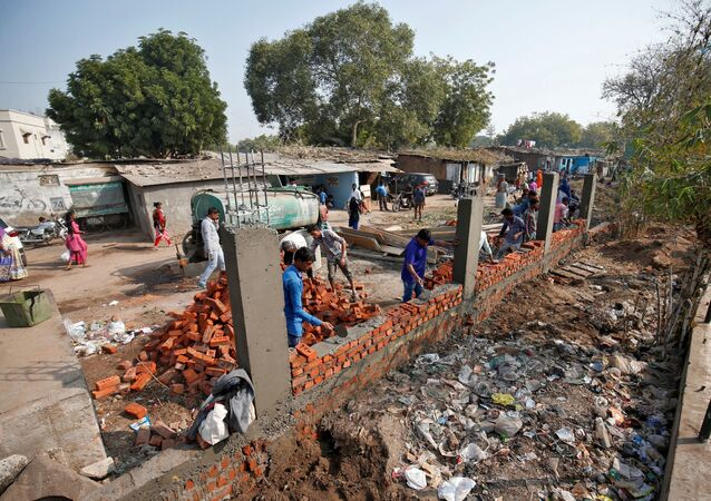 Construction workers build a wall along a slum area as part of a beautification drive along a route that U.S. President Donald Trump and India's Prime Minister Narendra Modi will be taking during Trump's visit later this month, in Ahmedabad, India, February 13, 2020