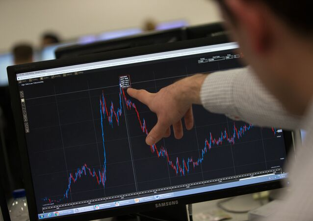 A trader points to a trading screen displaying today's record high for the FTSE 100, at ETX Capital in central London, England (File)