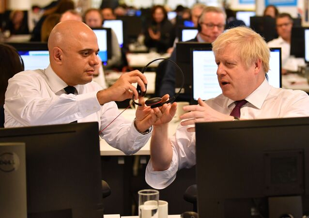 In this file photo taken on December 08, 2019 Britain's Chancellor of the Exchequer Sajid Javid (L) passes a headset to Britain's Prime Minister Boris Johnson (R) so that he can speak to a supporter as they man the phones at the Conservative Campaign Headquarters Call Centre in central London on December 8, 2019.