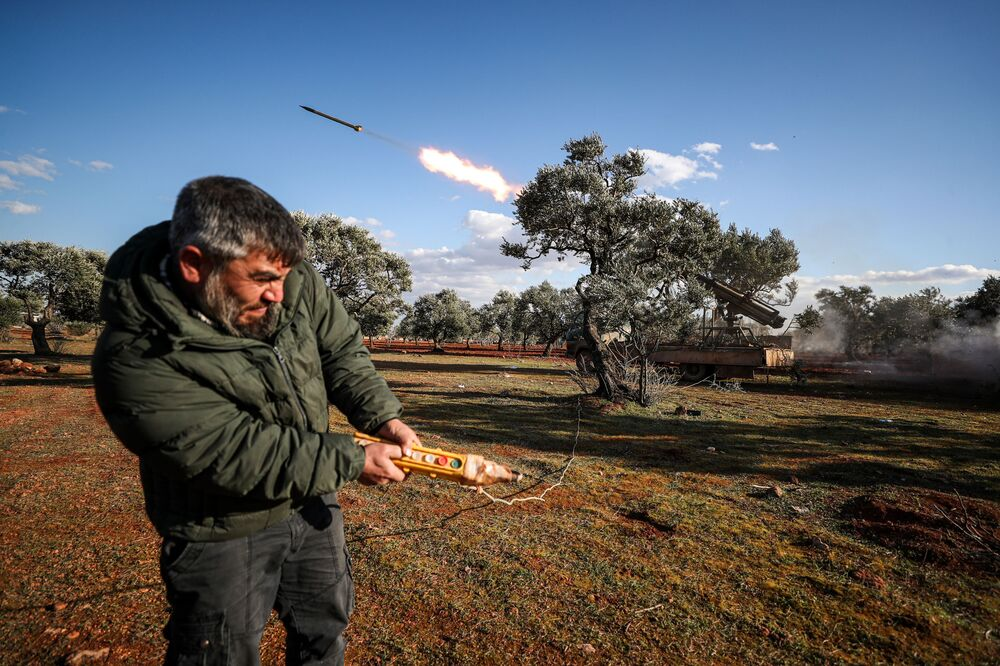 A Syrian rebel fighter remotely-fires a rocket from a truck-mounted launcher at a position in the countryside of Idlib towards regime forces positions in the southern countryside of Syria's Aleppo province on February 10, 2020.