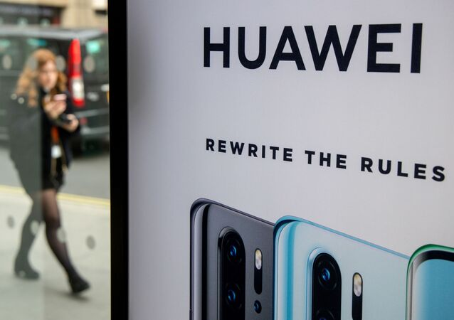 (FILES) In this file photo taken on April 29, 2019 A pedestrian walks past a Huawei product stand at an EE telecommunications shop in central London