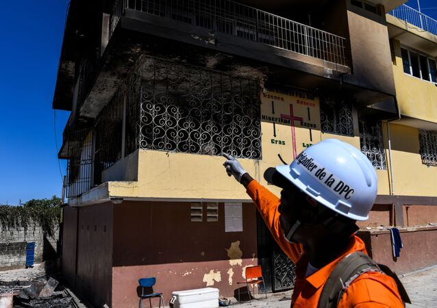 A firefighter points at the Orphanage of the Church of Bible Understanding where a fire broke out the previous night in the Kenscoff area outside of Port-au-Prince February 14, 2020.