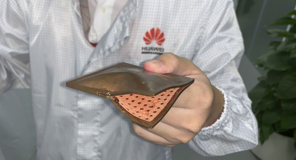 A Huawei research engineer holds up a thermal cooling solution with copper structure at the Huawei Materials lab in Dongguan in Southern China's Guangdong province