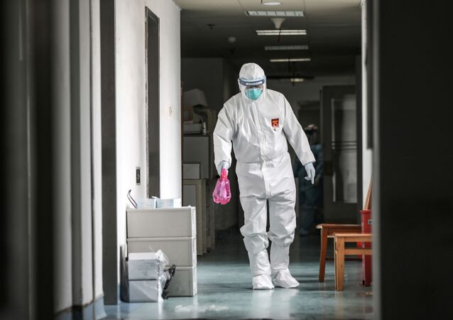 A medical worker in protective suit disinfects the hallway at Jinyintan hospital in Wuhan