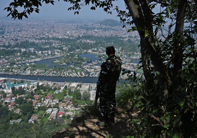 An Indian paramilitary trooper patrols at the top of a hill in Srinagar on August 25, 2019.