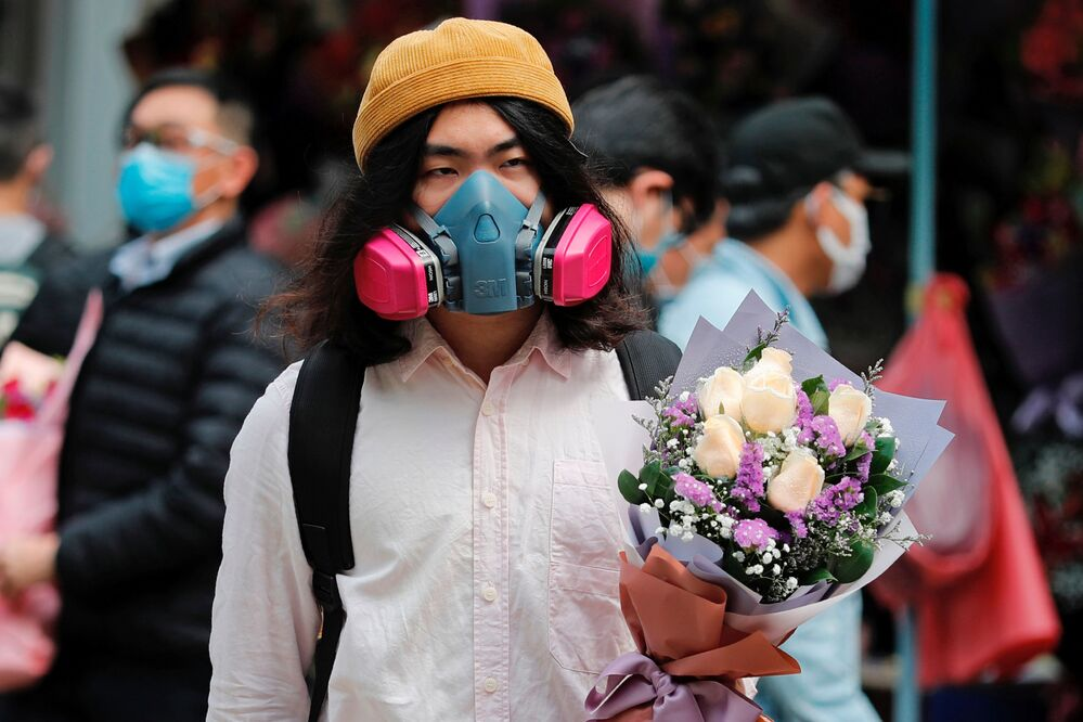 A man wears a gas mask as he holds a bouquet of flowers, following the outbreak of the novel coronavirus on Valentine's Day in Hong Kong, China February 14, 2020.