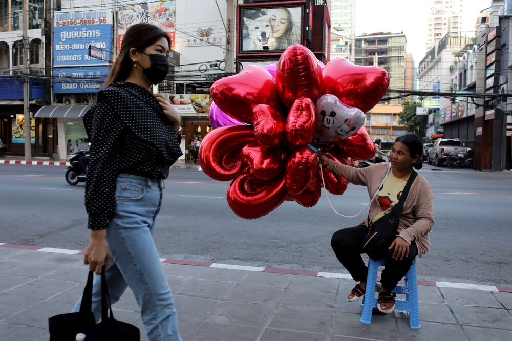 A woman wearing a protective mask walks past a woman selling balloons to celebrate Valentine's Day in Bangkok, Thailand February 13, 2020.