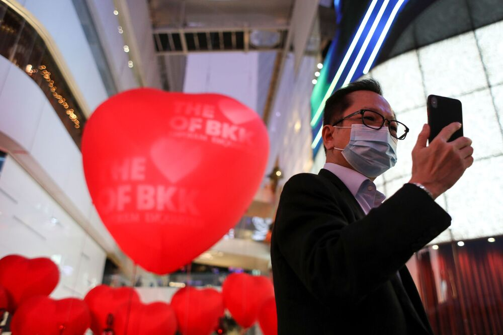 A man wearing a protective mask takes a selfie in front of hearts celebrating Valentine's Day in front of a shopping mall in Bangkok, Thailand February 13, 2020.