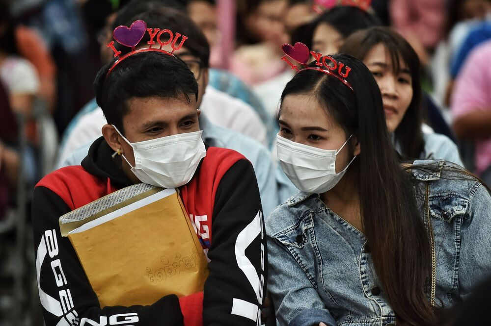 A couple in protective facemasks wait to register their marriage licence on Valentine's Day in Bang Rak, the Thai capital's district of love, in Bangkok on February 14, 2020.