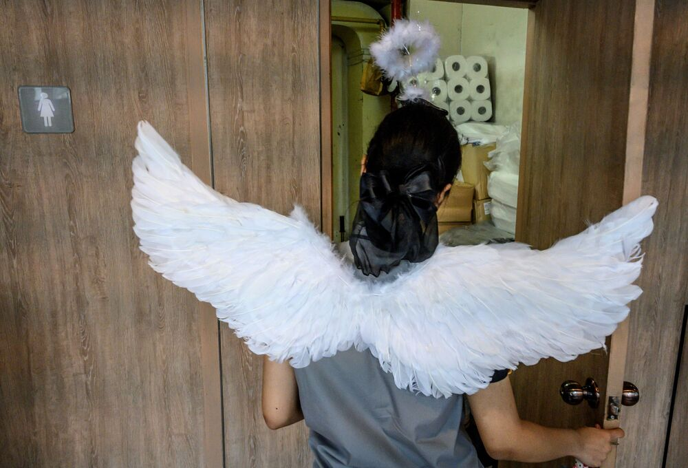 An employee of a fast-food chain wears angel wings to celebrate Valentine's Day in Bangkok on February 14, 2020.