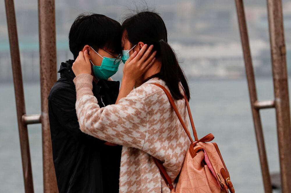 A couple wears masks as they embrace, following the outbreak of the novel coronavirus on Valentine's Day in Hong Kong, China February 14, 2020.