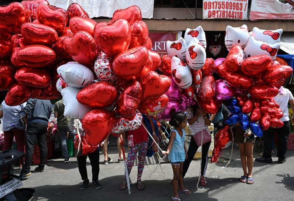 Vendors selling heart-shaped balloons wait for customers on Valentine's day at a flower market in Manila on February 14, 2020.