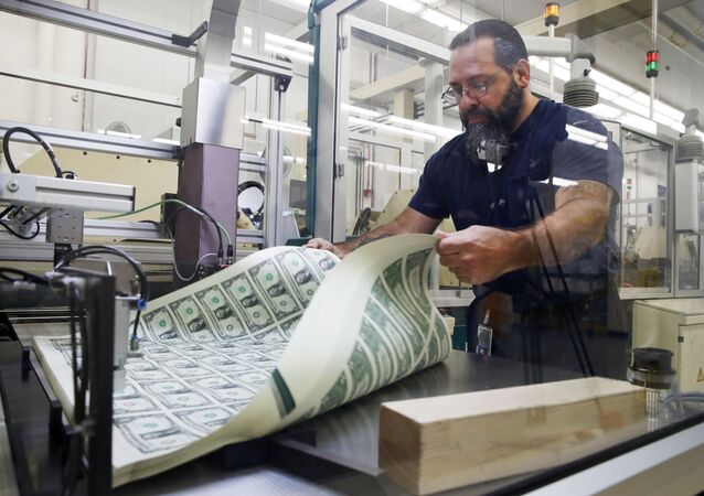 FILE- In this Nov. 15, 2017, file photo, a worker aerates printed sheets of dollar bills at the Bureau of Engraving and Printing in Washington.