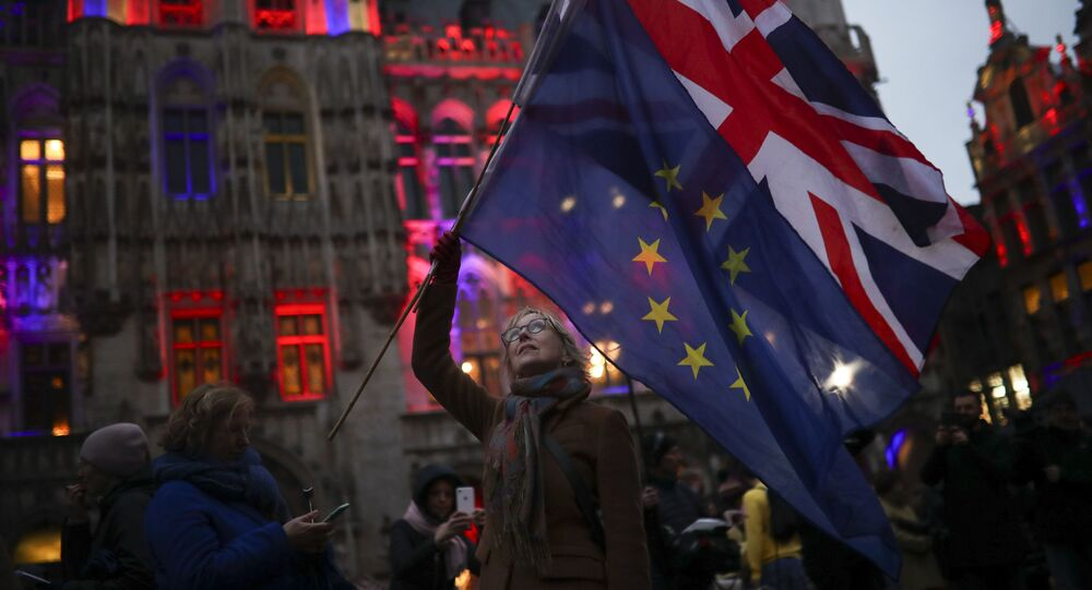 A woman holds up the Union and the European Union flags during an event called Brussels calling to celebrate the friendship between Belgium and Britain at the Grand Place in Brussels, Thursday, Jan. 30, 2020.