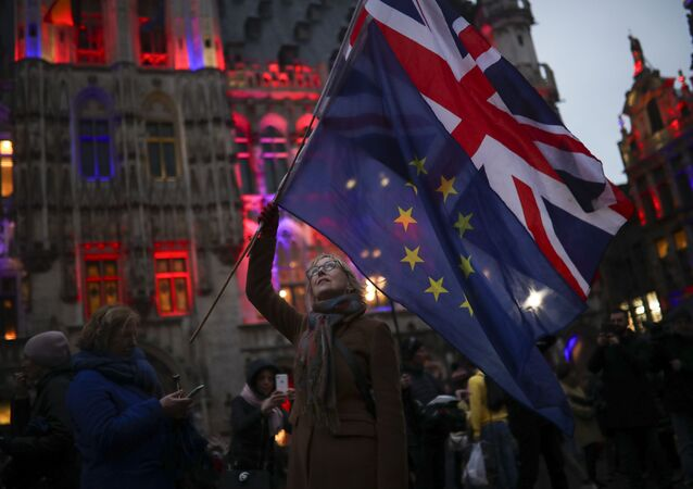 A woman holds up the Union and the European Union flags during an event called Brussels calling to celebrate the friendship between Belgium and Britain at the Grand Place in Brussels, 30 January 2020.