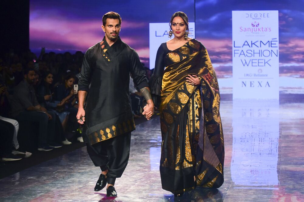 Bollywood actors  Karan Singh Grover (L) and Bipasha Basu present creations by Sanjuktta Dutta during the Lakme Fashion Week 2020 Summer/Resort fashion show in Mumbai on February 14, 2020.