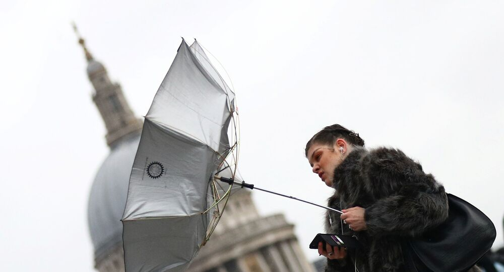 A woman struggles with an umbrella as she walks in front of St Paul's Cathedral during storm Dennis in London, Britain, February 15, 2020.