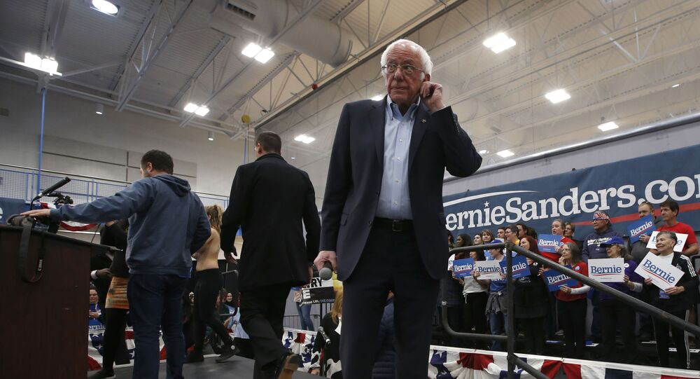 Democratic presidential candidate Sen. Bernie Sanders I-Vt., waits as campaign workers remove protestors from the stage during his campaign event in Carson City