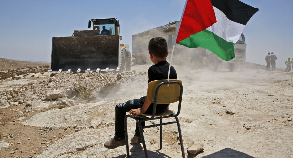A Palestinian boy sits on a chair with a national flag as Israeli authorities demolish a school site in the village of Yatta, south of the West Bank city of Hebron and to be relocated in another area, on July 11 2018.