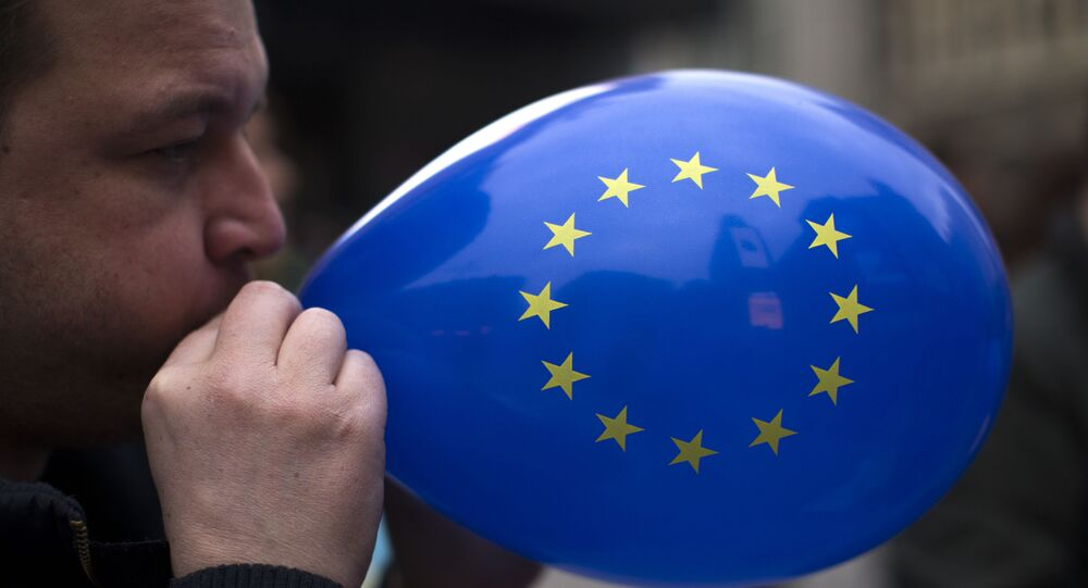 A man inflates a balloon with the flag of the European Union during a gathering to celebrate the 60th anniversary of the European Union in Madrid, Saturday, March 25, 2017.